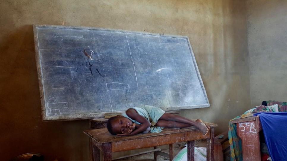 Rebecca deitada sob uma mesa na sala de aula onde moram provisoriamente