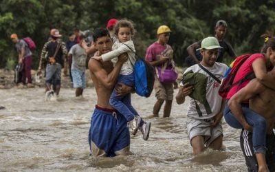 Venezuelanos cruzam rio inundado para buscar comida na Colômbia