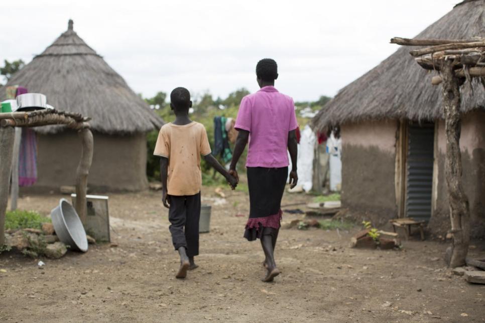 A refugiada sul-sudanesa Rose* caminha com seu filho de 10 anos no assentamento Bidibidi, em Uganda. No dia em que ela tentou suicídio, em julho de 2019, seu filho foi quem a resgatou