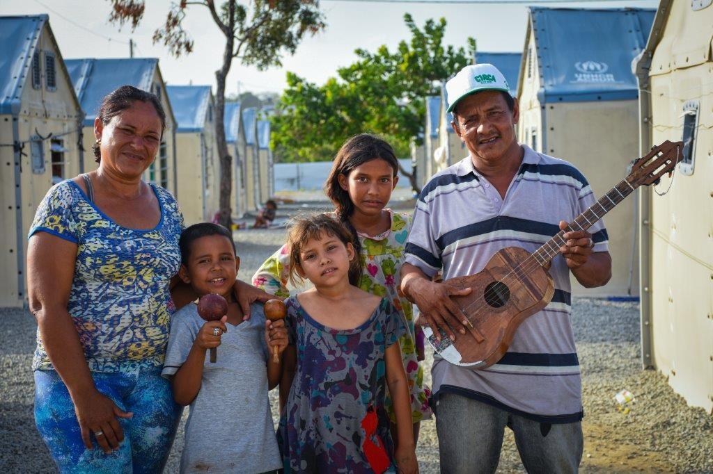 """O músico e pai Guillermo Martine segurando o seu """"cuatro"""", sua esposa Katty Pereira e seus três filhos, sendo o mais novo Anrel segurando seus """"macarates"""""""
