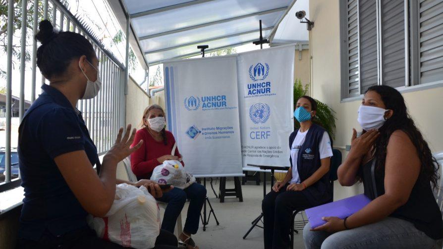 Francis (esquerda) e Sliany (direita), acompanhada da sua mãe, conversam com funcionária do IMDH durante entrega do cartão do programa CBI em Brasília