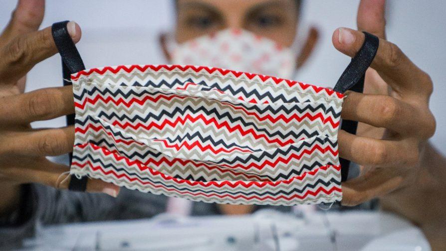 José Alexandre mostra máscara que costurou