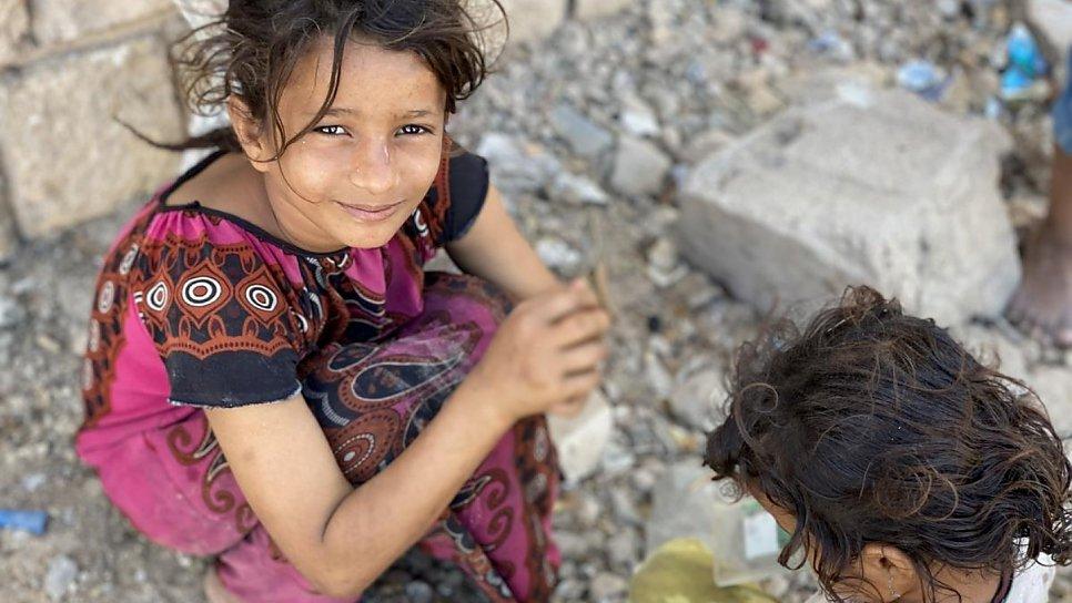 Nesta foto de fevereiro de 2020, Ipteehal, 9, brinca com sua irmã do lado de fora do prédio inacabado, onde moram com outras famílias deslocadas em Al Mukalla, no Iêmen