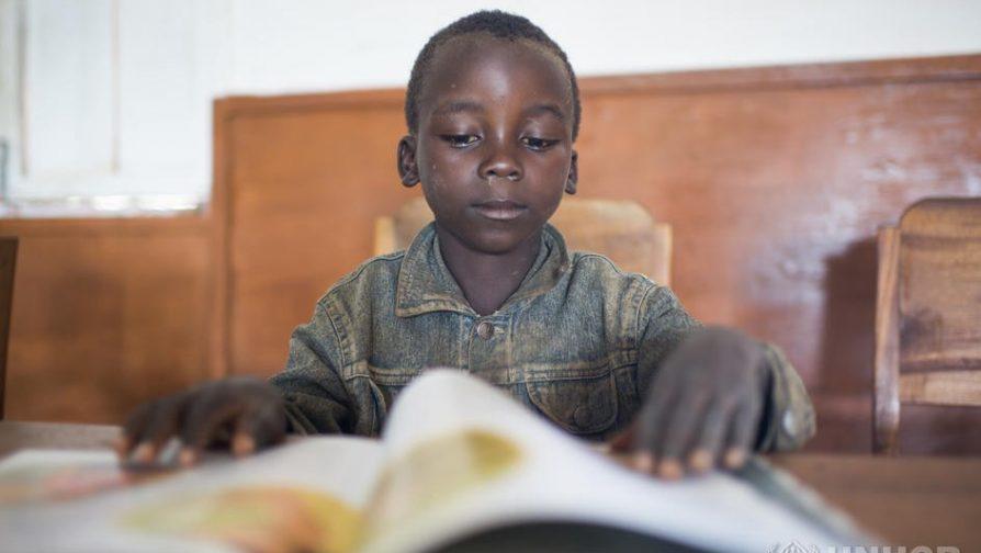 Jacques, 8, refugiado do Burundi, lê um livro no campo de refugiados de Lusenda, no sul do Kivu, na República Democrática do Congo