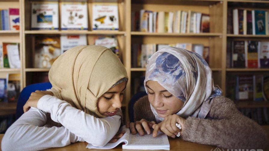 Ariam (à esquerda) e Amneh (à direita) leem juntas um livro na biblioteca do campo de refugiados de Za'atari, na Jordânia