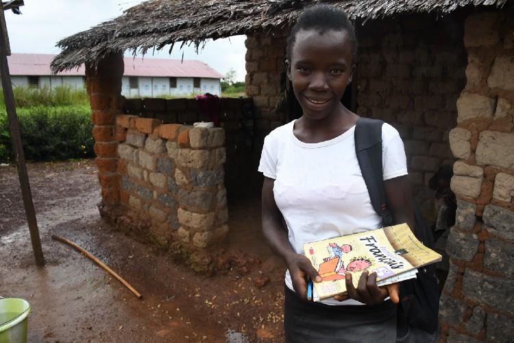 Refugiada de 15 anos no campo de Inke na República Democrática do Congo (RDC) se preparando para uma aula com distanciamento social ministrada pelo professor local Jean Aime Mozokombo