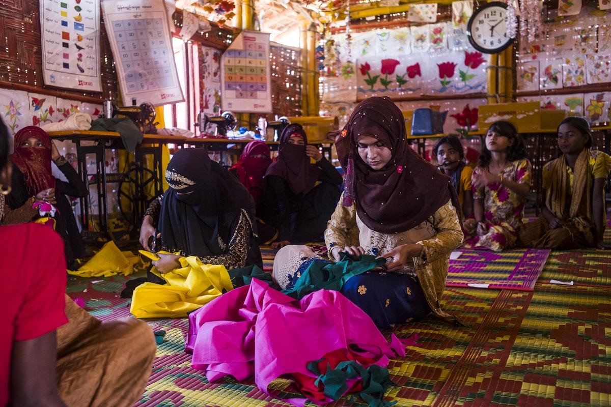 Saima (12) e sua irmã Humaira (20) cortaram tecidos para fazer flores como parte de uma atividade do Clube de Adolescentes Naf