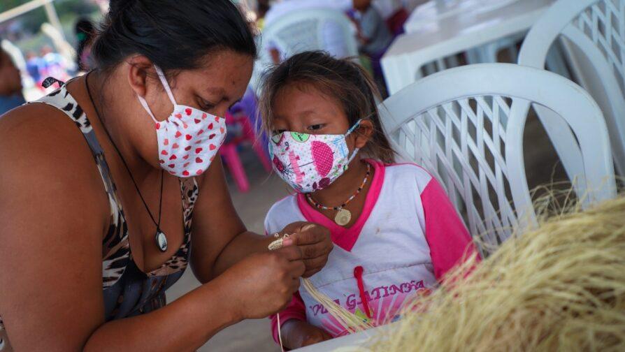 Mãe ensina sua filha a arte tradicional de trançar fibra de buriti no abrigo Pintolândia, em Boa Vista (RR)