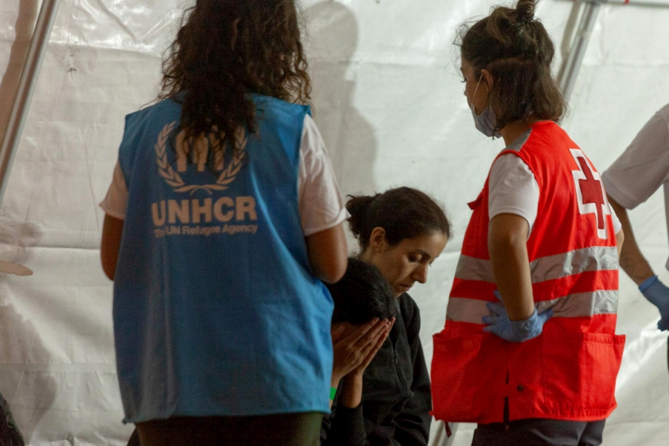 Una trabajadora de ACNUR asistiendo a refugiados y migrantes rescatados en España.