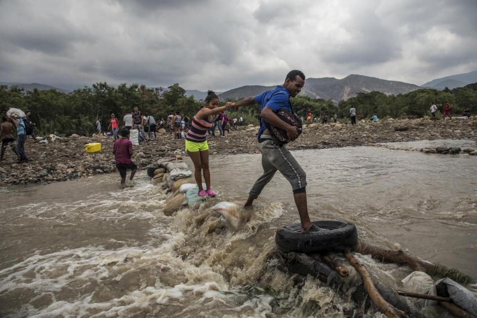 Personas venezolanas cruzan el río Táchira para buscar comida y seguridad en Cúcuta, Colombia.