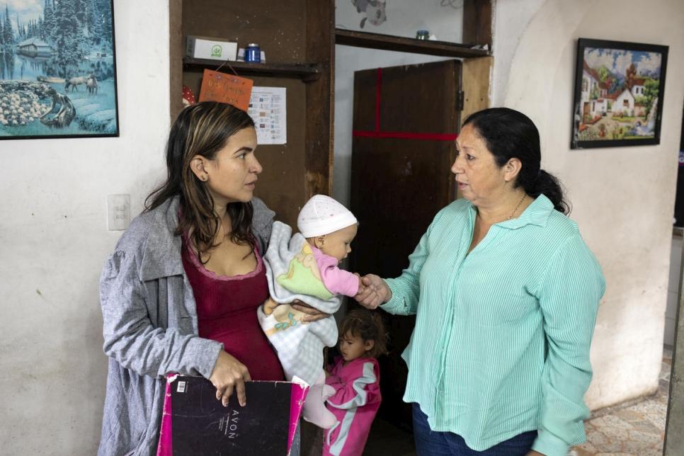 Marta Duque advierte a una mujer venezolana con sus hijos sobre las dificultades que podrían encontrar en su viaje por la montaña.