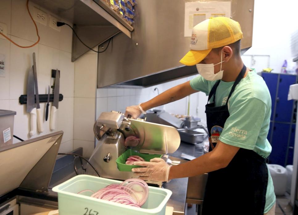 César cortando y preparando las cebollas para el día en la hamburguesería Sierra Nevada.