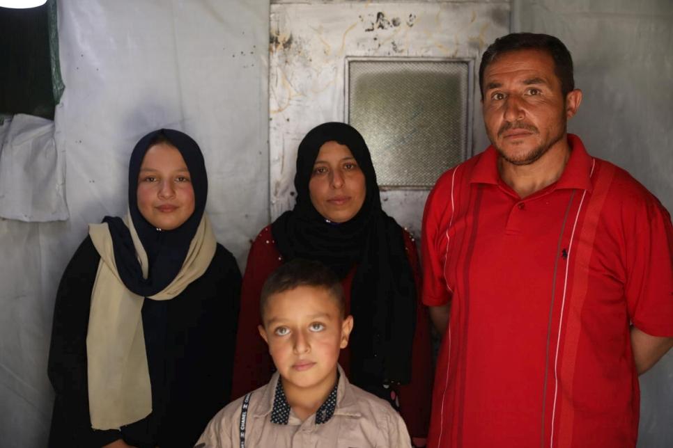 Khalil (derecha) con su familia, incluida su hija Nahed (izquierda), de 12 años, que abandonó la escuela para ganar dinero recogiendo verduras.  © ACNUR / Houssam Hariri