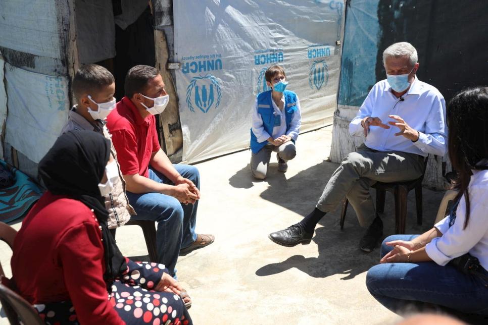 Grandi habla con Khalil y su familia fuera de su casa en un asentamiento informal de tiendas de campaña en el valle de Bekaa en el Líbano.  © ACNUR / Houssam Hariri